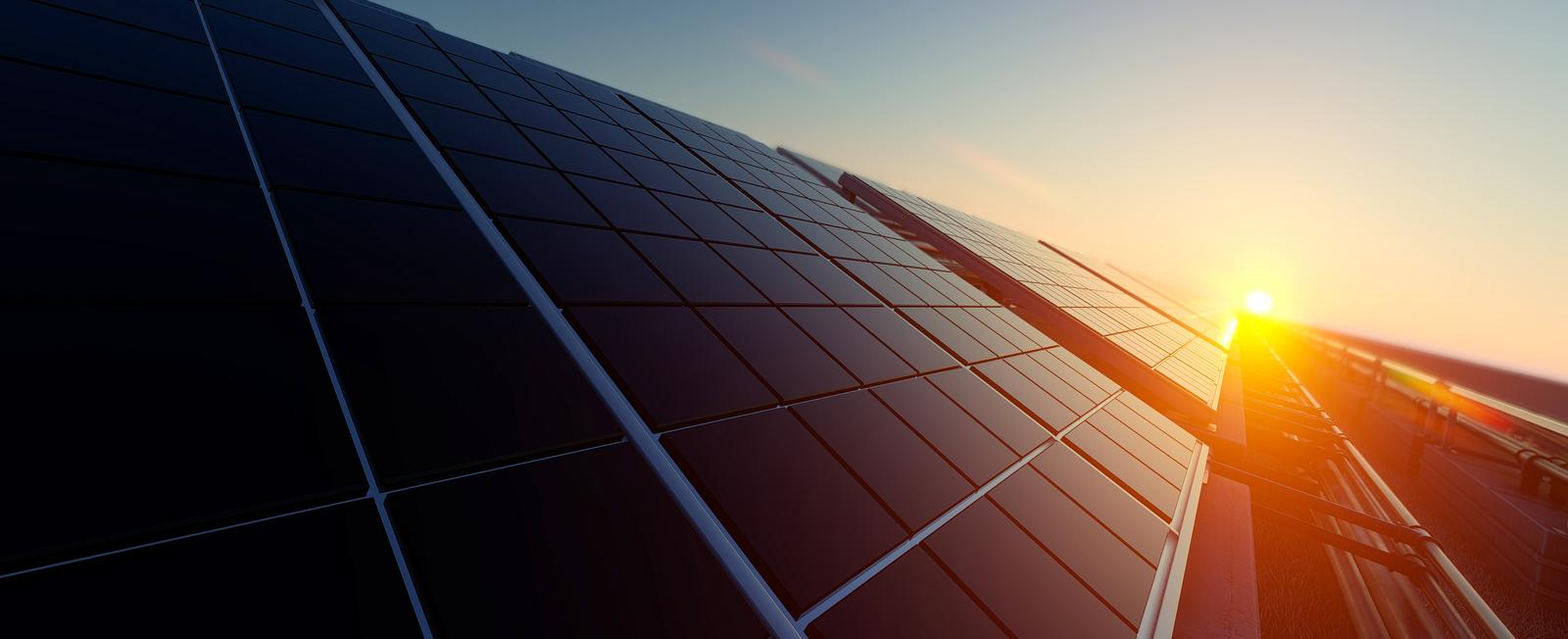 sun setting on black solar panel system