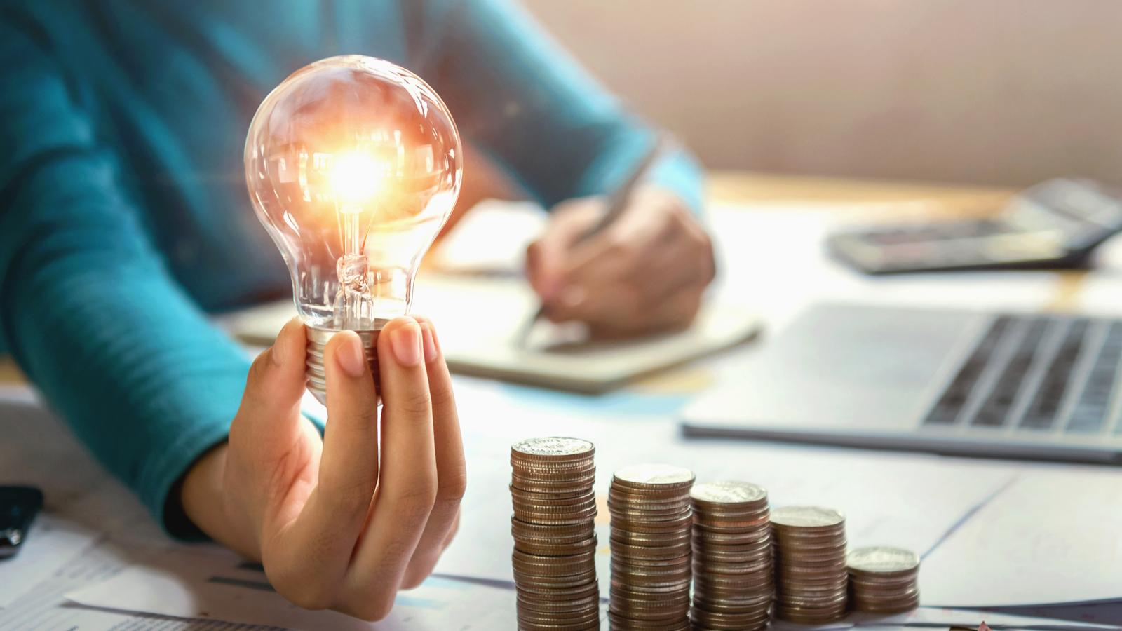 Woman Calculating Finances and Holding Lightbulb with Stack of Coins on Table